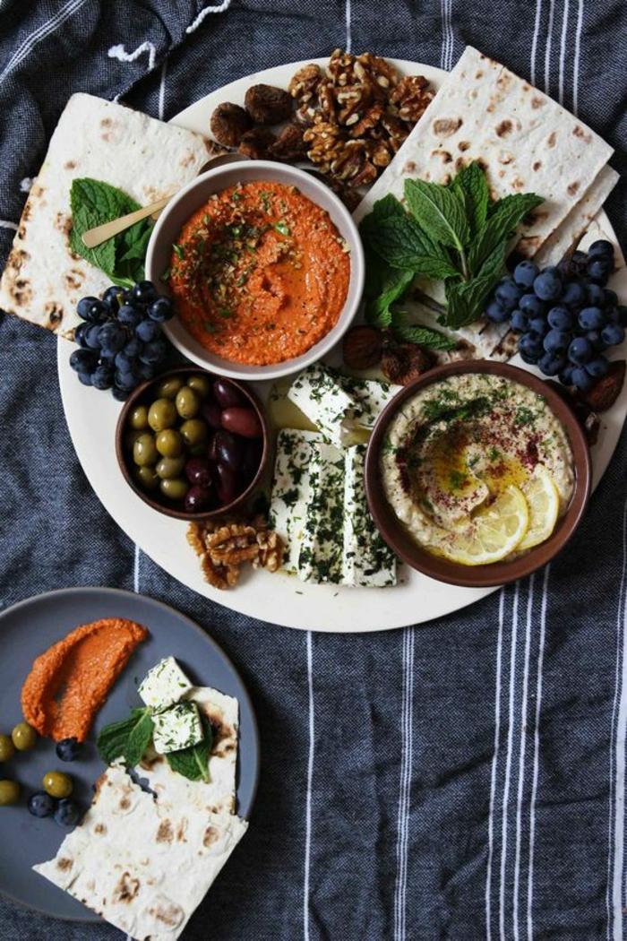 un plateau antipasti exotique servi avec de la sauce piquante mouhamara et de baba ganoush libanaise