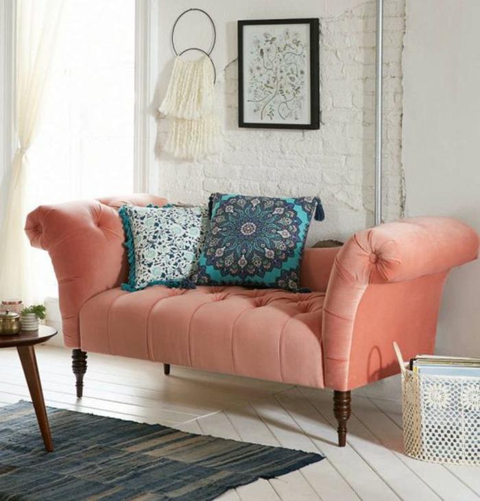 sofa couleur saumon, mur en briques blanches, coussins boho chic, planches de sol blanches