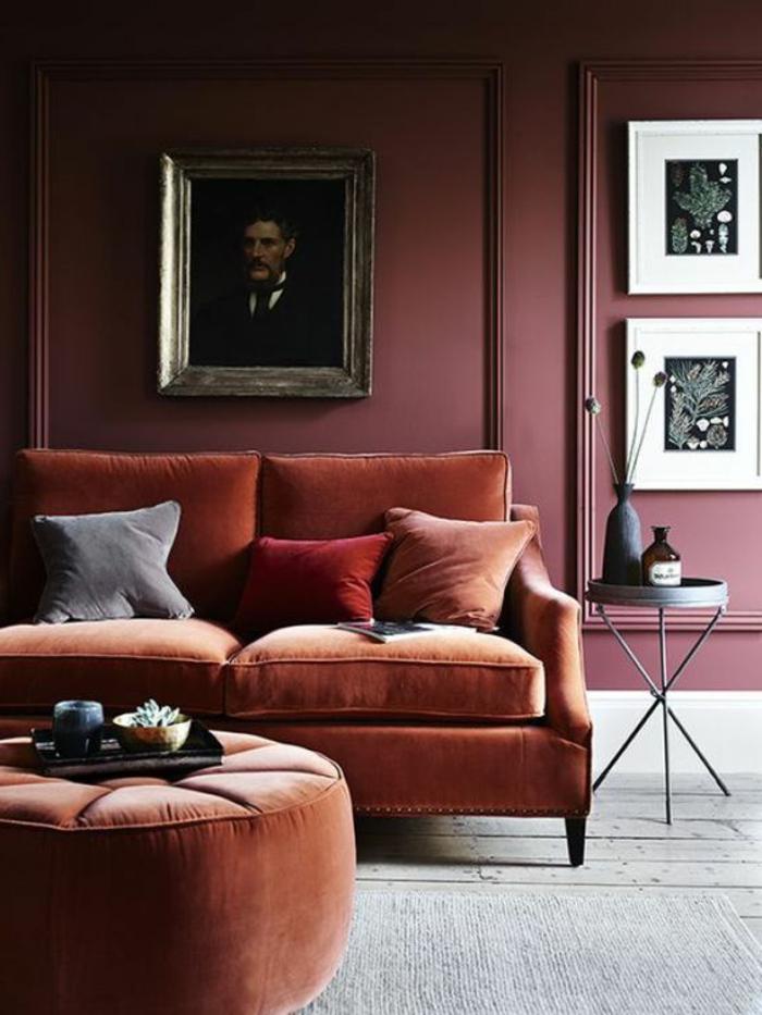 pouf et sofa couleur saumon, mur pourpre, portrait encadré et peintures monochromes, table tripode