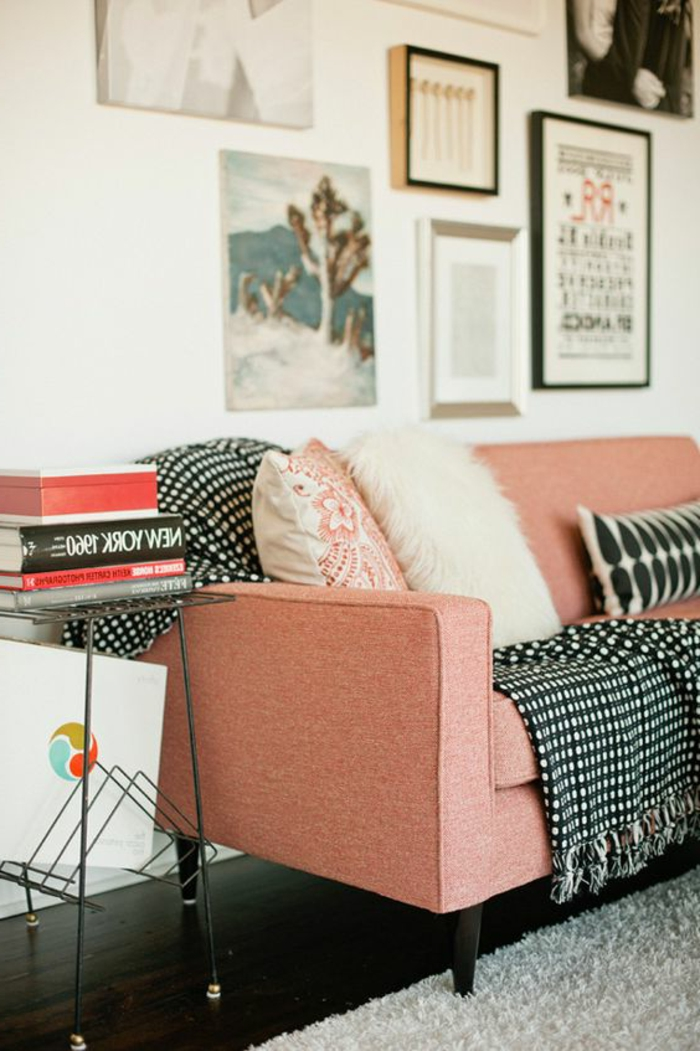 sofa rose saumon, coussins décoratifs, tableaux encadrés, petit chevet avec des livres
