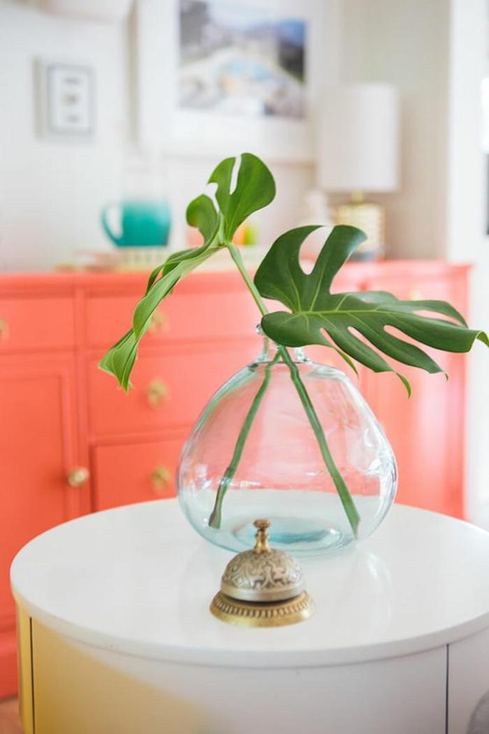 sofa rose saumon, table blanche ronde et décoration avec feuilles vertes, commodde saumon