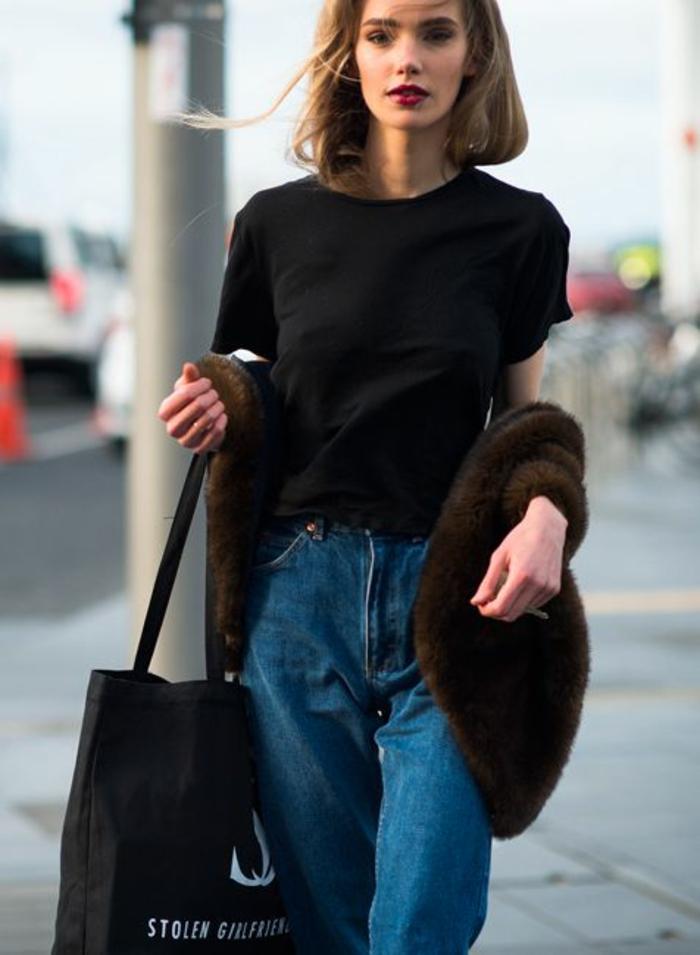 mode année 80 jean bleu foncé taille haute avec T shirt noir simple et veste fausse fourrure manches courtes