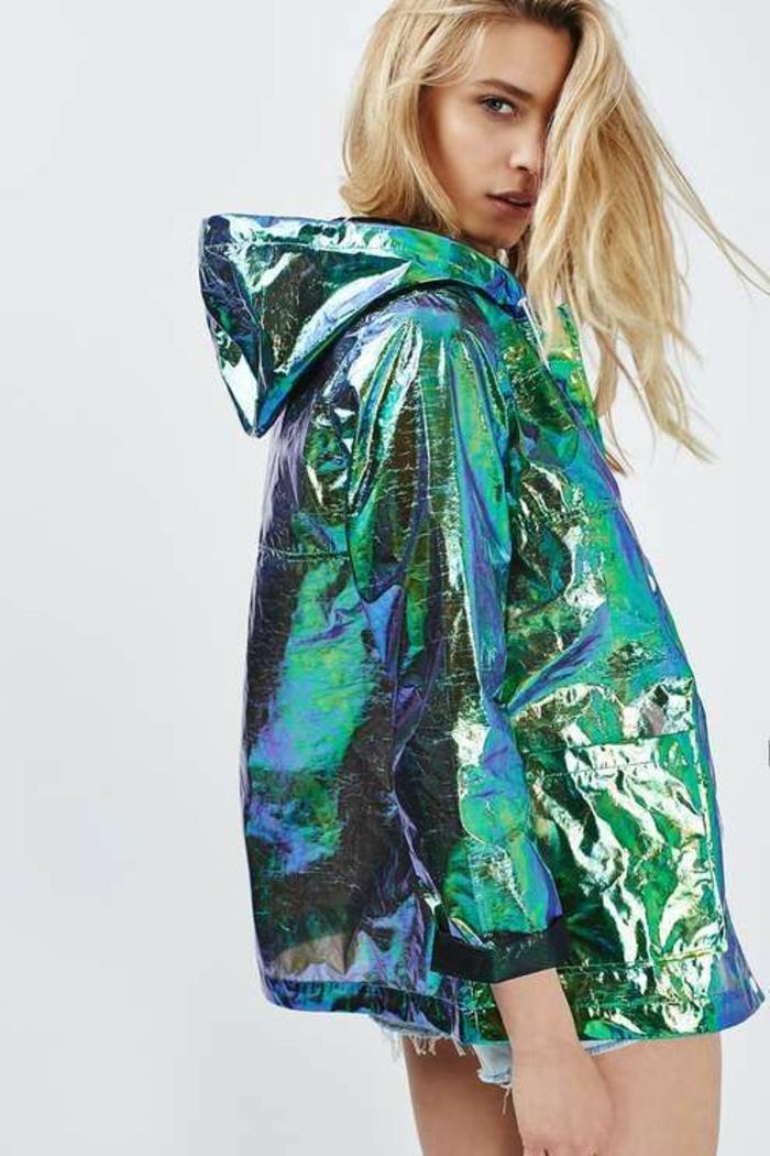 mode année 80 veste aux reflets et nuances bleu et vert irisés avec capuche avec des shorts bleu denim clair aux ourlets déchirés