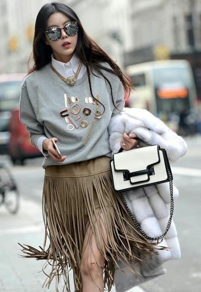 mode année 80 jupe à franges couleur taupe avec gros blouson en gris clair et sac avec chaine métallique