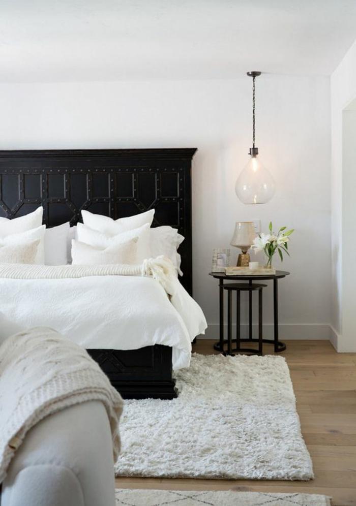 une chambre à coucher élégante en noir et blanc au décor vintage, une suspension chevet en verre