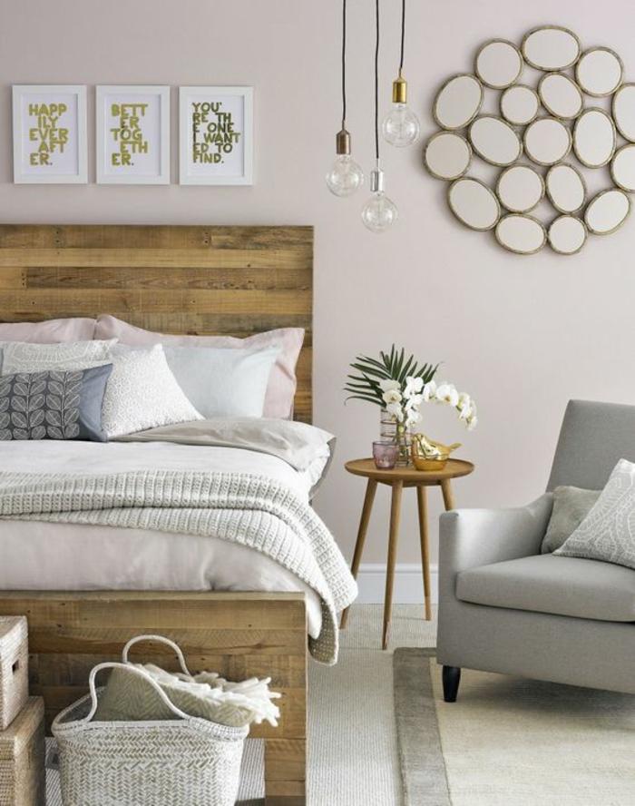 une suspension à trois ampoules au-dessus d'une table de chevet trépied en bois, chambre à coucher à déco douce