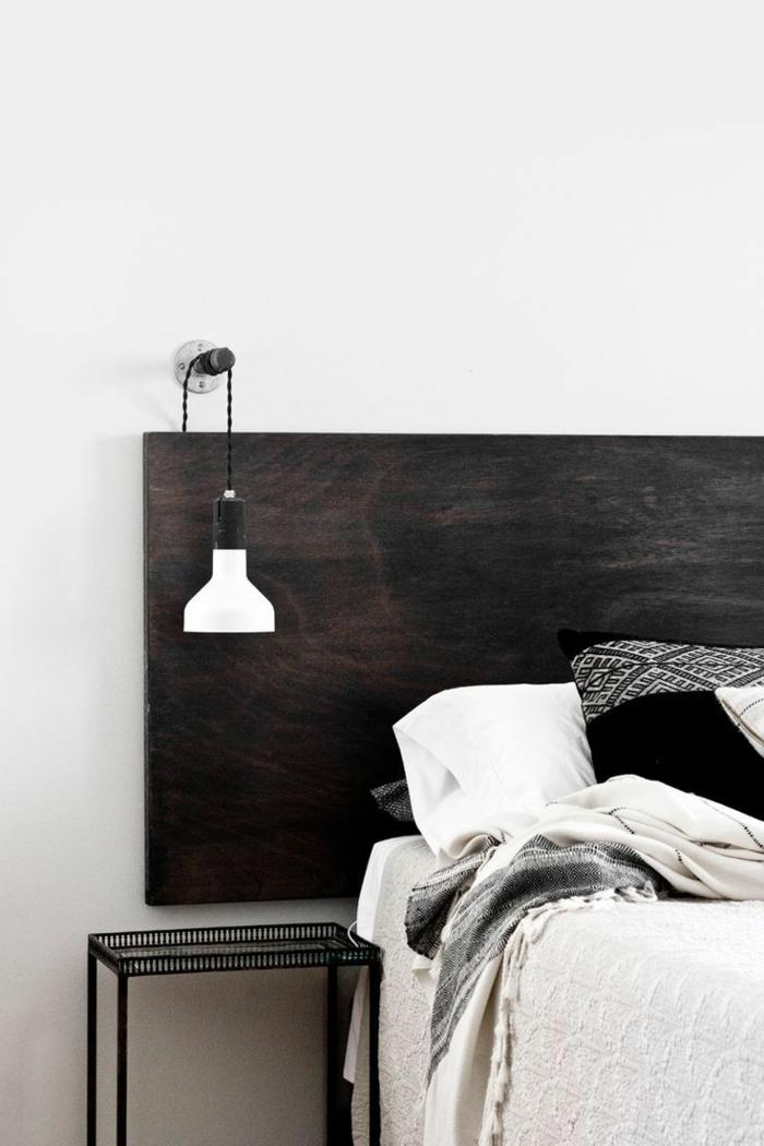 joli contraste entre la tête de lit en bois foncé et la suspension chevet blanche