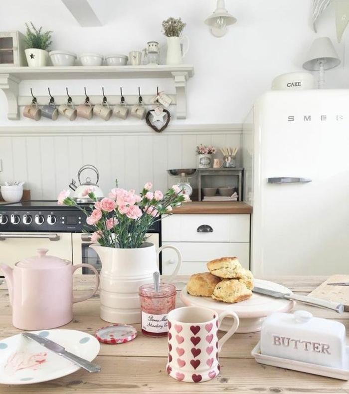 exemple de table campagne chic en bois, façade cuisine et frigo blancs, vaisselle et tasses, decoration de fleurs rose
