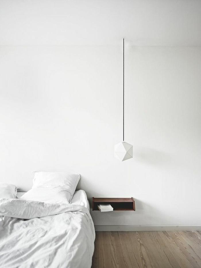 un luminaire suspension géométrique blanche en forme de diamant suspendue au-dessus d'une table de chevet flottante