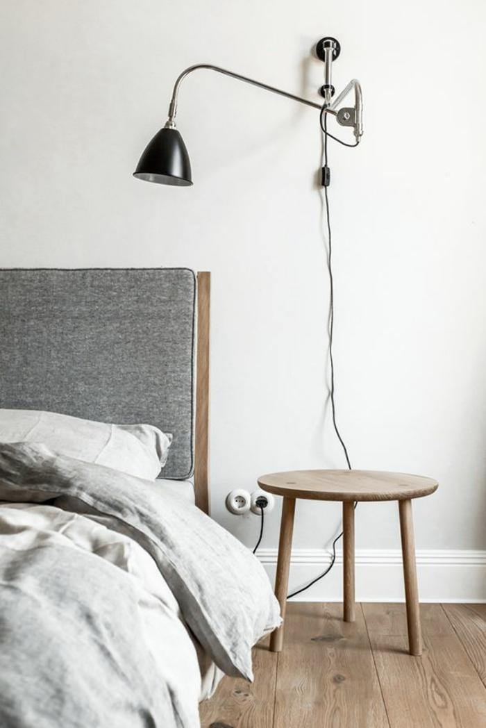 une lampe d'applique avec bras réglable au-dessus d'un trépied en bois naturel, chambre à coucher monochrome