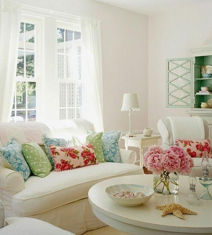 canapé et table en bois blancs, coussins multicolores, bouquet de pivoines, vaisselier vert pastel, rideaux blancs