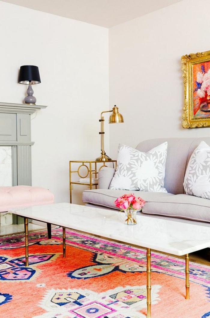 tapis couleur corail, cadres dorés, grande table blanche, soga gris confortable