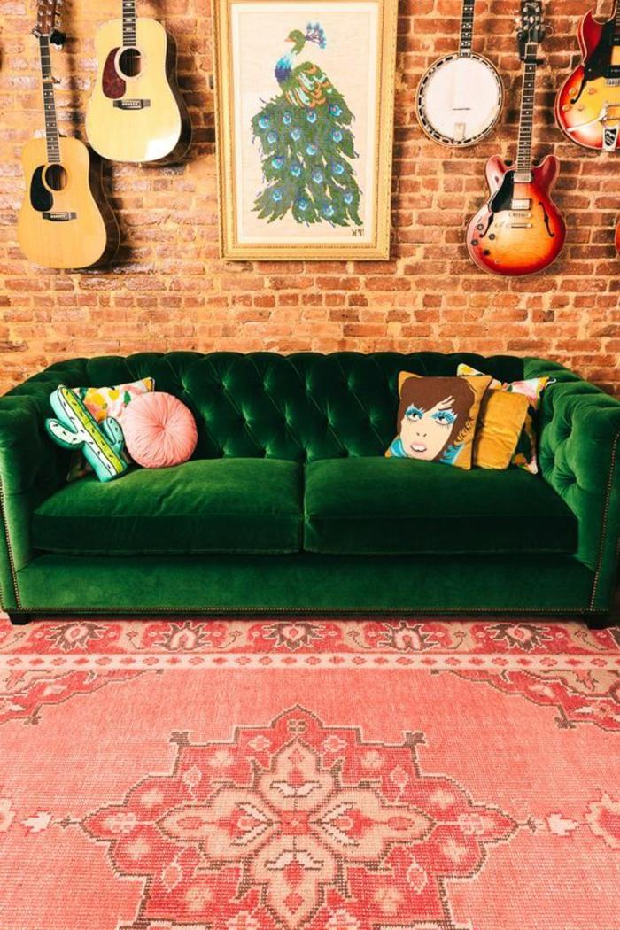 tapis couleur saumon, sofa verte capitonnée, mur en briques, guitares suspendues au mur