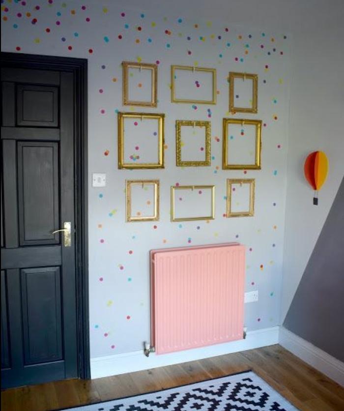 deco cadre vide, plusieurs cadres dorés, sur un mur décoré de points multicolores, tapis en noir et blanc, parquet marron, tapis en noir et blanc