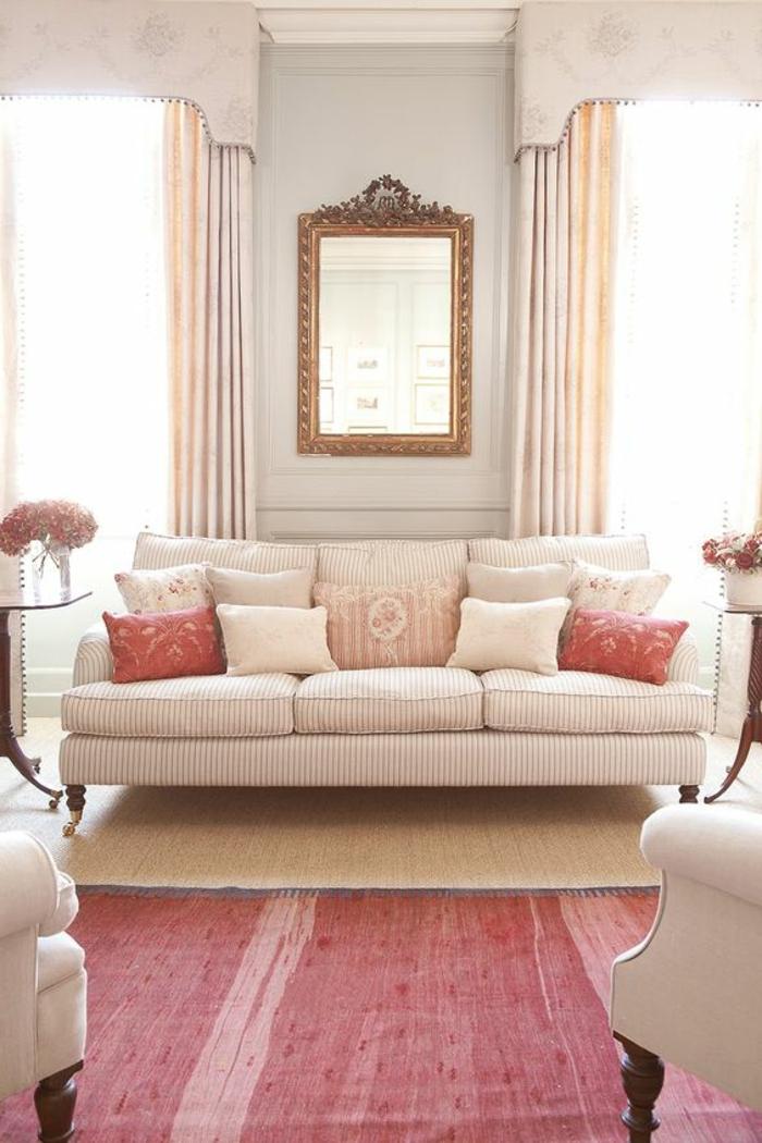 tapis rose saumon, sofa rose avec plusieurs coussins, miroir encadré