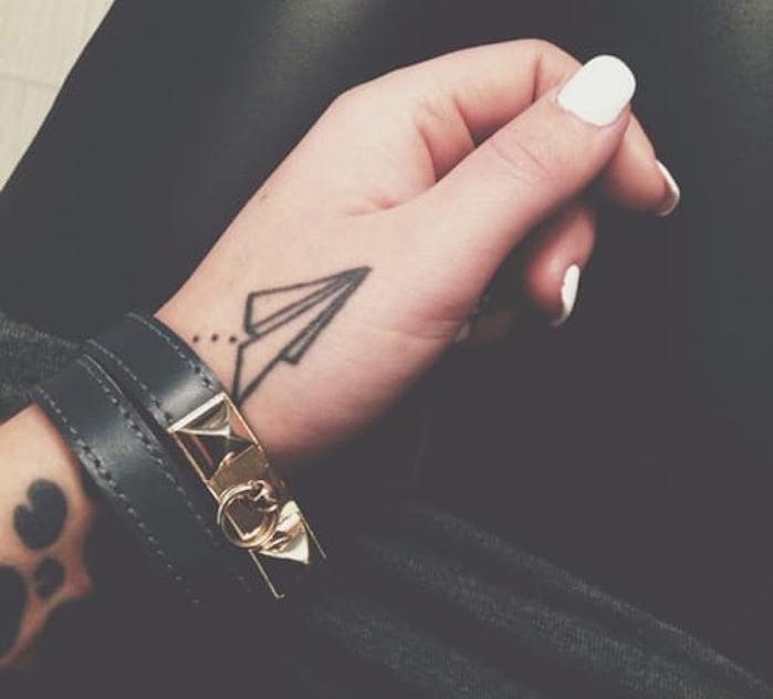 petit avion papier comme tatouage main minimaliste