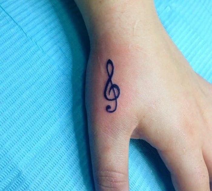 clé de sol tattoo sur le pouce tatouage main