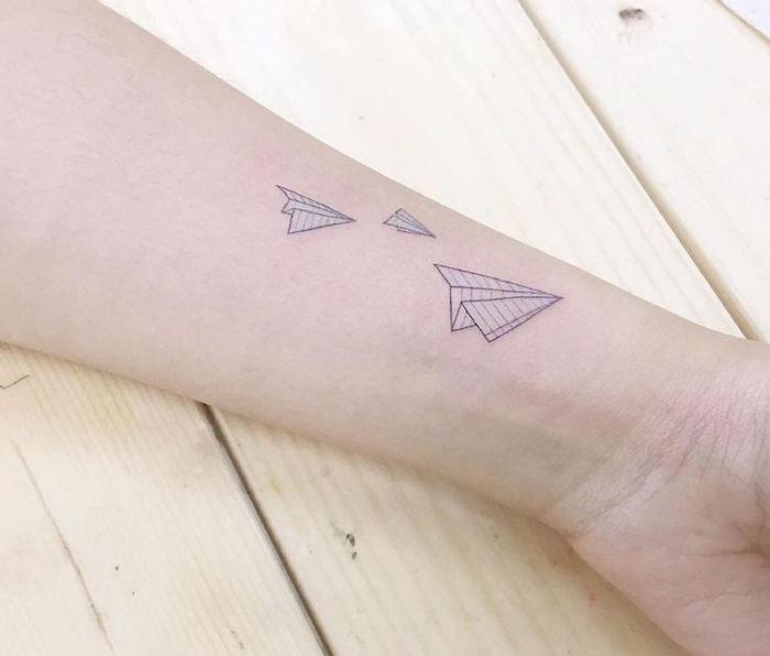 tattoo avions en papier style style encre bleue sur avant bras