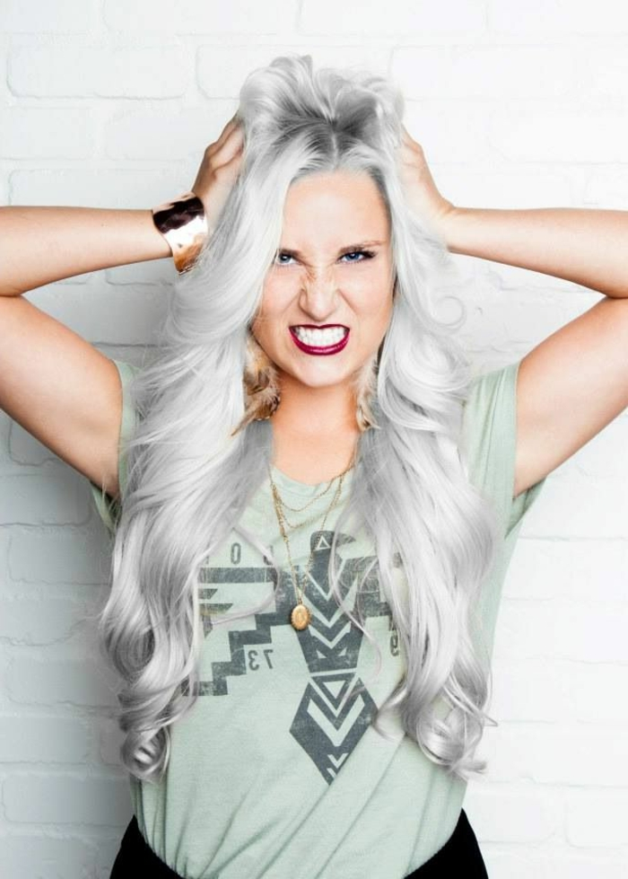 coloration cheveux gris cendré, bracelet doré, t-shirt vert pastel, boucles d'oreilles plumes, nuance de gris