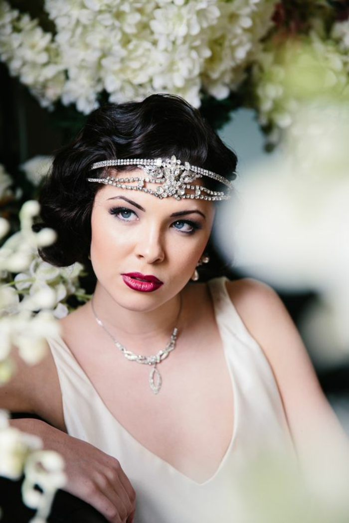 tenue gatsby, robe blanche décolleté en V, diadème argentée, jolis bouquets de fleurs