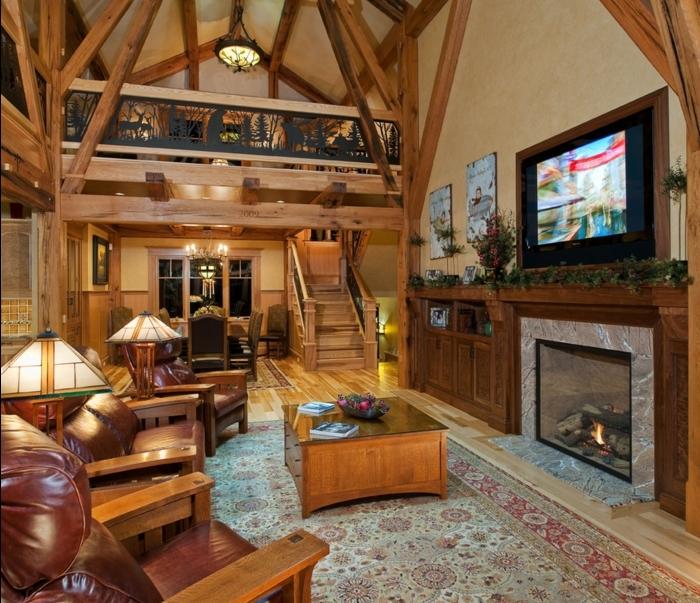 maison ossature bois, tapis à motifs orientaux, fauteuils en bois et cuir, cheminée rustique, parquet en bois clair, salon rustique