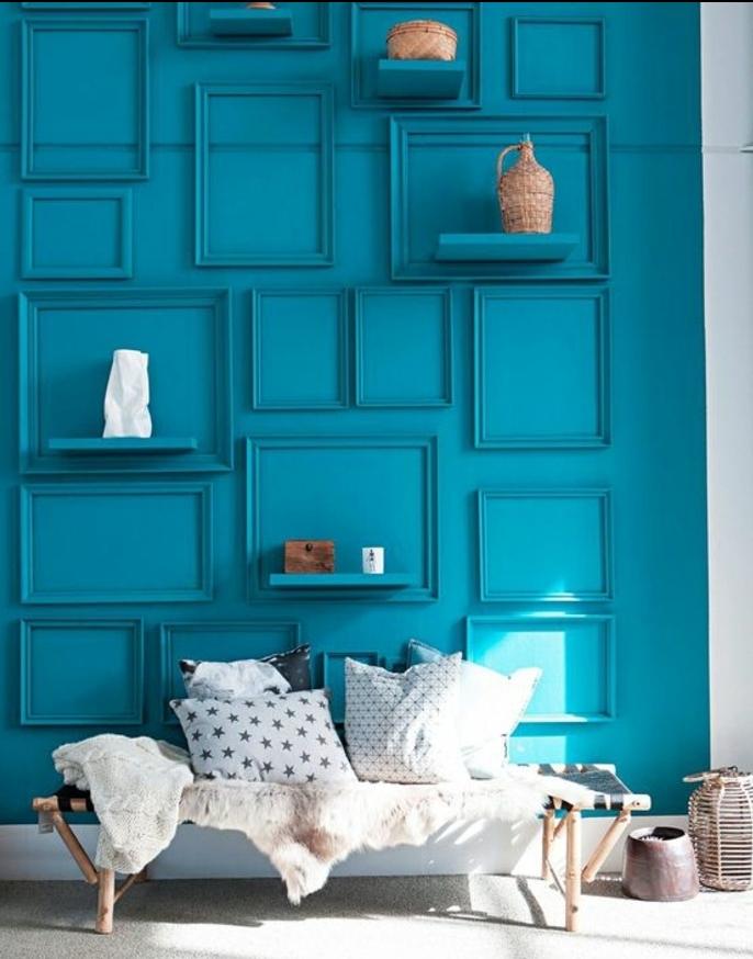 banc en bois style scandinave, couverture de fourrure, coussins en noir, blanc et gris, mur bleu décoré de cadres bleus, comment habiller un mur