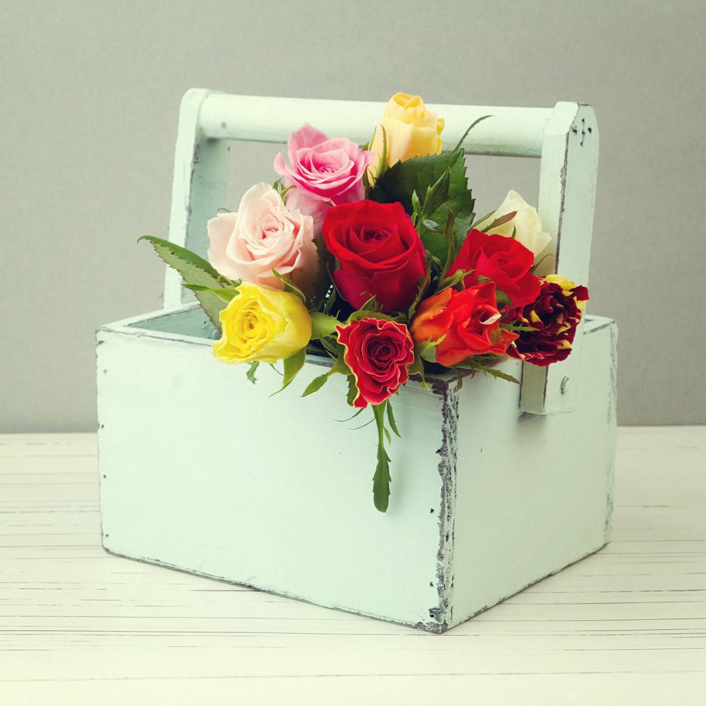 exemple de centre de table décoratif, shabby chic, un panier en bois, repeint de bleu paste, bouquet de roses de couleurs diverses, deco campagne chic