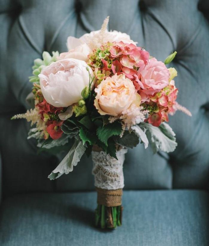 un bouquet de mariage pivoines et aures fleurs, tiges, serrés de dentelle blanche, idée décoration mariage