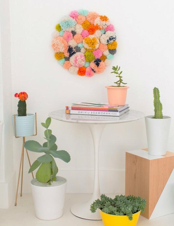 decoration murale, constituée de pompons multicolores, table d appoint blanche, plantes vertes, activité créative