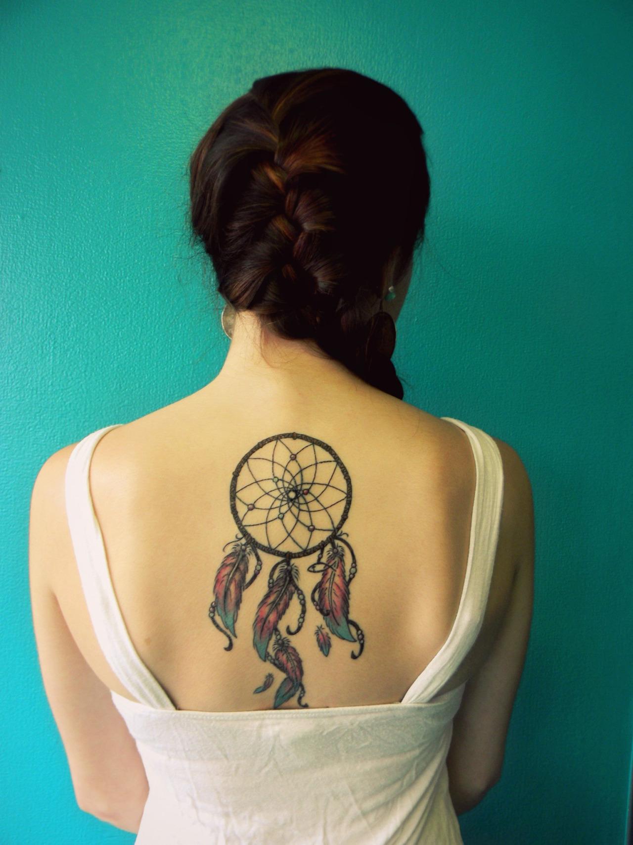 idée de tatouage attrape reve sur le dos, filet et cerceau rond, plumes en bleu, rouge, jaune et orange, femme tresse sur le coté