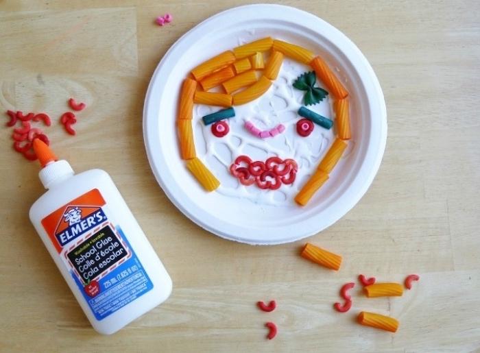 un dessin dans une assiette en plastique, des pâtes de couleurs diverses pour dessiner une tête de fille, activité manuelle primaire