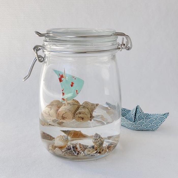 activité créative pour petits et grands, un voilier de bouchons de liège, un cure dent et papier pour la voile, decoration coquillages dans un pot en verre, mason jar crafts