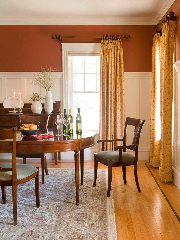 une salle à manger couleur sienne brûlé en harmonie avec le mobilier en bois et les nuances de l'ocre