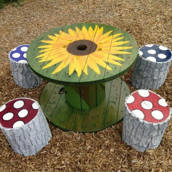 amnagement jardin aire de jeux pour enfants, tabourets en bûche de bois, décoré à pois, table repeinte en vert, dessin motif tournesol