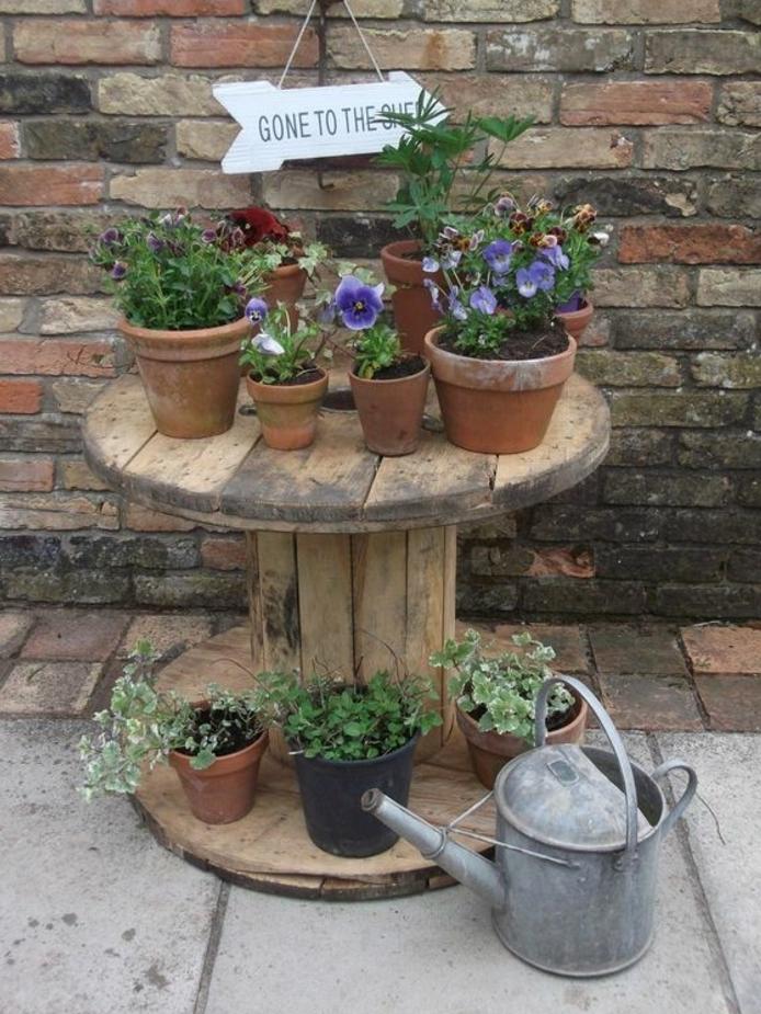 deco exterieur, amenagement jardin, table en touret bois brut, rangement pour pots de fleurs, mur en briques