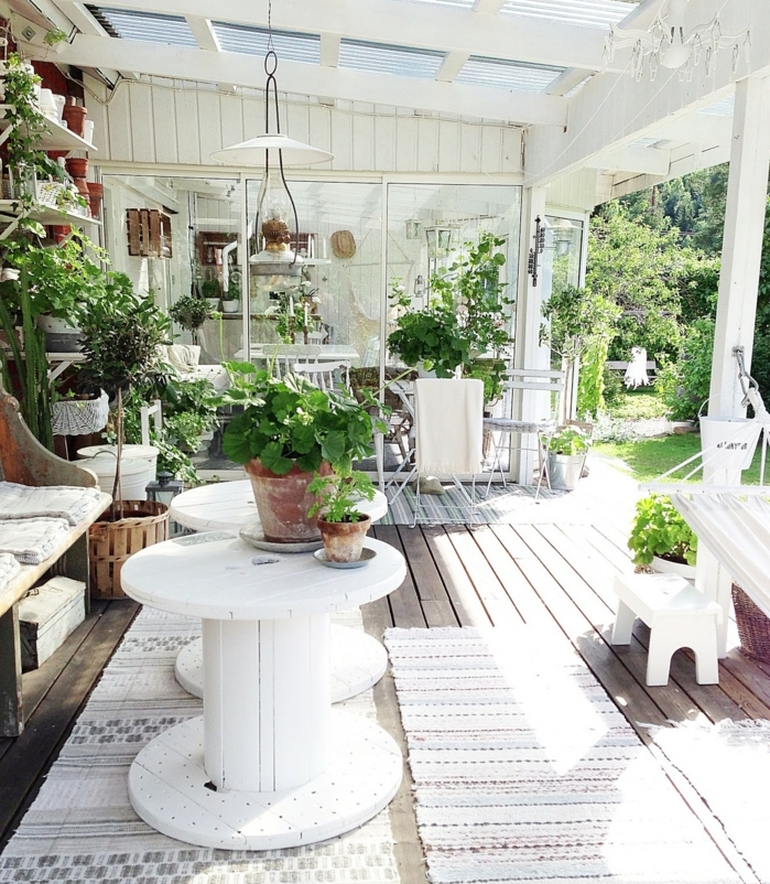 amenagement terrasse, deco exterieur, table en touret, banc en bois avec coussins d assise, tables repeintes en blanc, decoration plantes vertes, suspension originale, que faire avec un touret