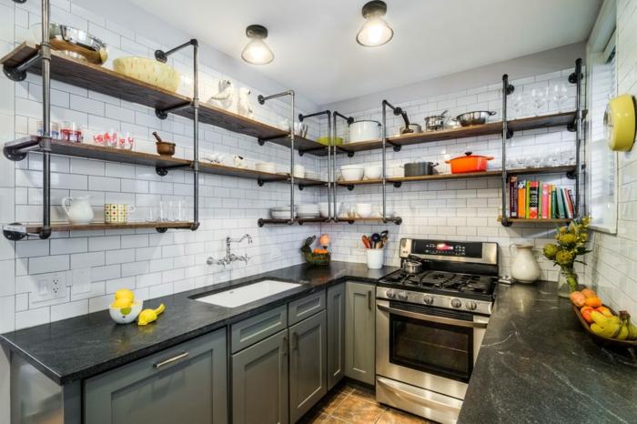 etagere industrielle, commode de cuisine en vert, bol à fruits, horloge jaune, tasses de café, murs blancs, comptoir noir