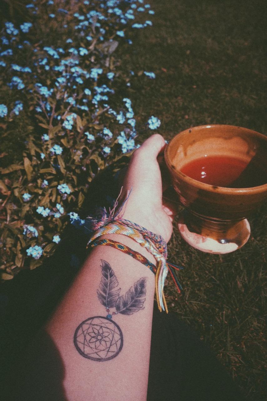 tatouage attrape reve avant bras, contours, cerceau, filet et plumes noires, bracelets colorés, cadre naturel