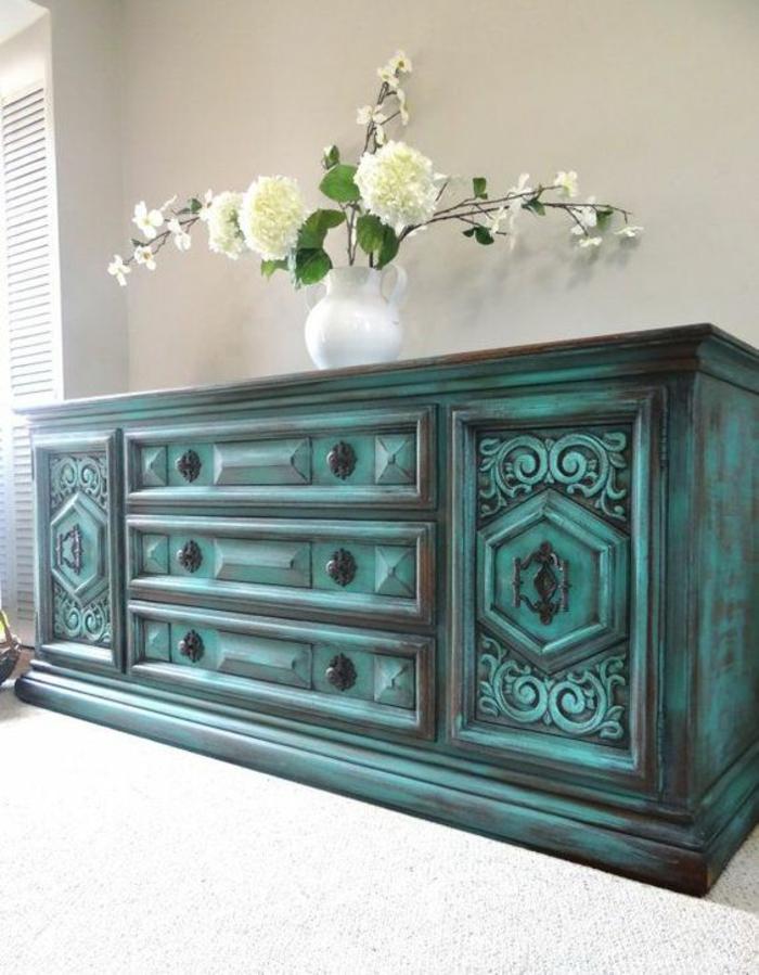 meuble baroc en vert effet vieilli pour l'entrée avec un vase blanc de fleurs printannières