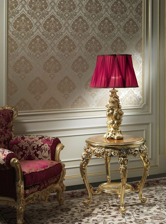 meuble baroque avec fauteuil vermeil et motifs dorés et mur au tissu satiné motifs fleurs de lys