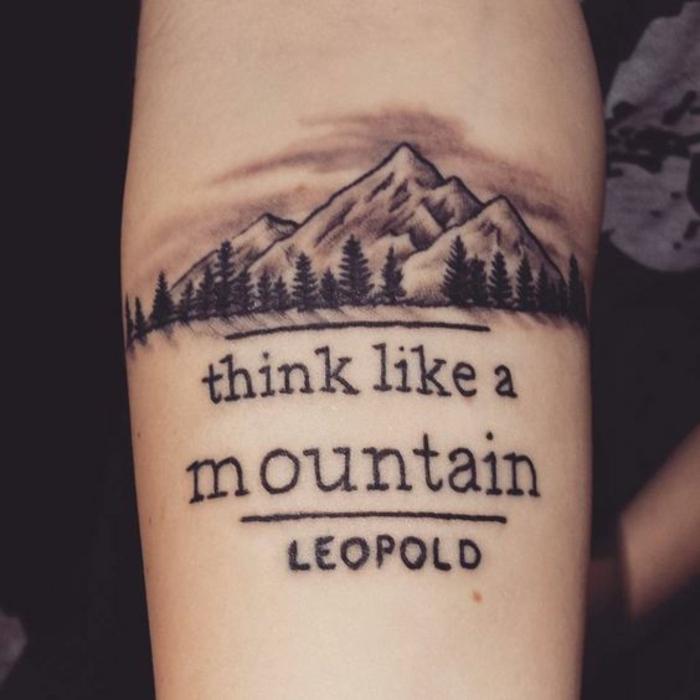 beau tatouage, montagne avec un script inspirant, forêt de sapins aux pieds de la montagne