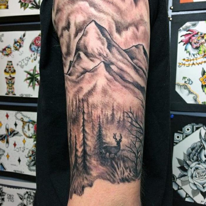 beau tatouage manche, forêt et cerf, montagne tatouée sur le bras d'un homme