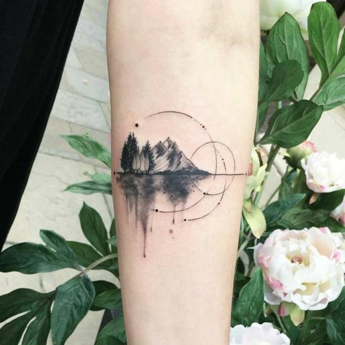 beau tatouage sur le bras, montagne et forêt, cercles inachevés, réflexions de la montagne