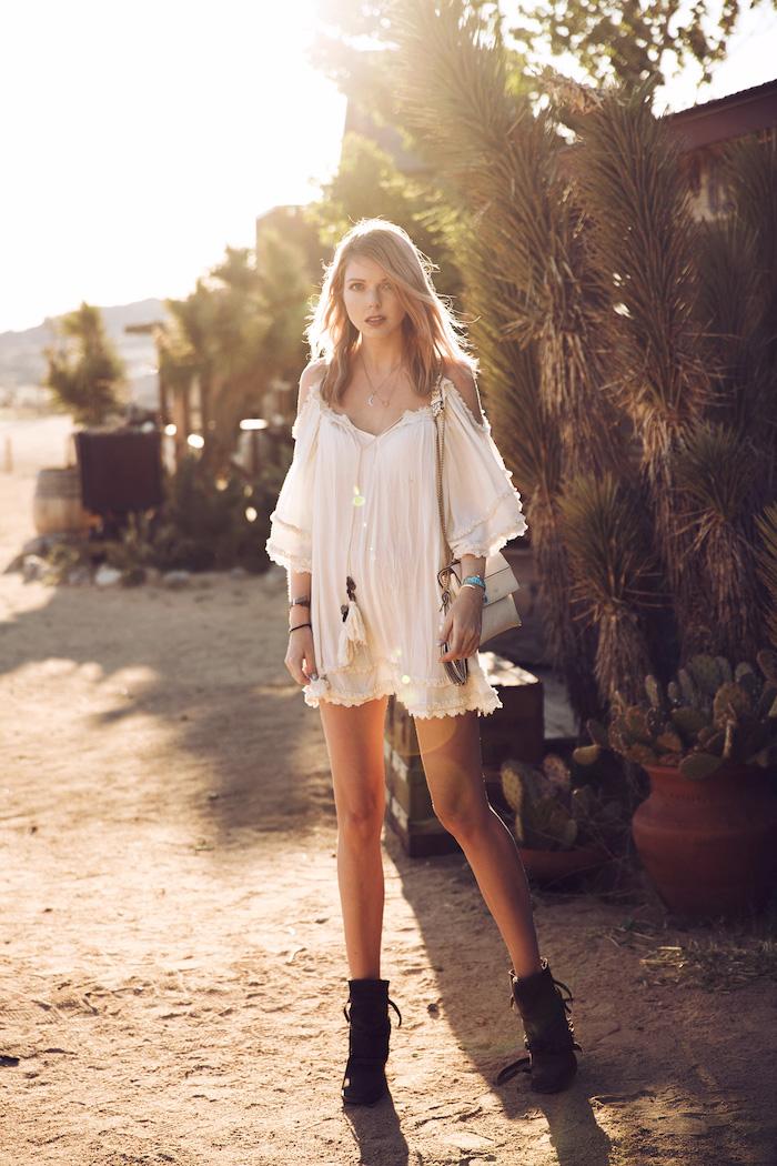 vetement boheme, collier avec pompons, bracelet ethnique, pochette beige, cheveux mi longs, femme dans le désert