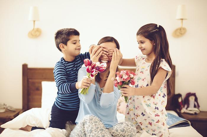 idee cadeaux, enfants avec leur mère, suprise au lit, blouse bleue, petite fille, bouquet de fleurs, lampes blanches