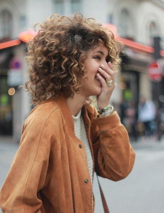 carré boucle femme métisse, blouson fauve, mèches blondes, modele de coiffure cheveux bouclés
