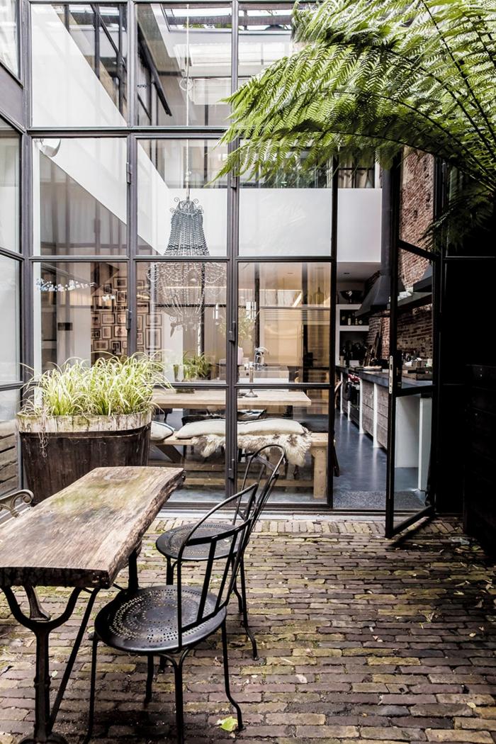 table basse industrielle, décoration extérieur, plante verte, grandes fenêtres, plancher en pierres, idee deco industrielle