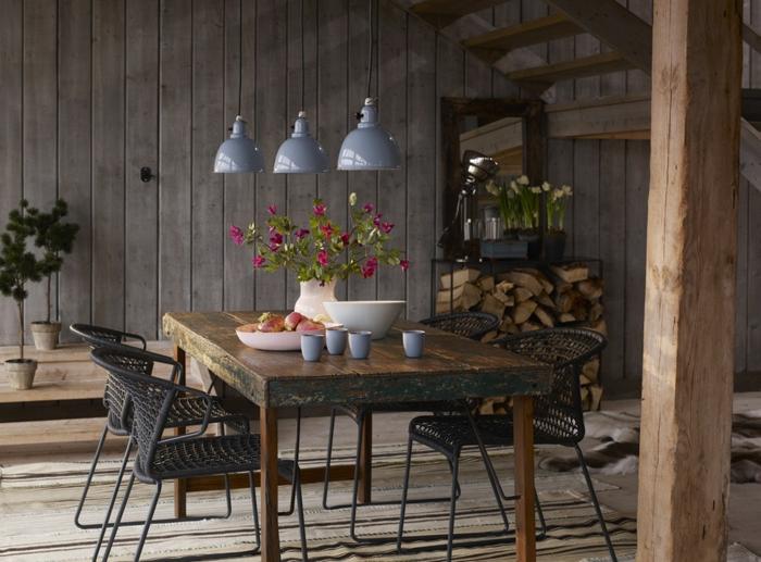 idee deco industrielle, table en bois massif, chaises noires, escalier en bois, lampes suspendues en bleu, bol à fruits