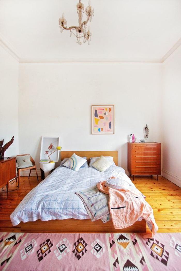 tissu exotique, tapis aztèque couleur rose, commode en bois, plafonnier avec pampilles, tableaux abstraits