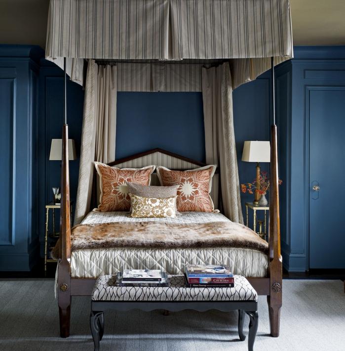 une chambre à coucher de style masculine en bleu marine et vert olive, un lit à baldaquin aux tons neutres, coussins couleur sienne